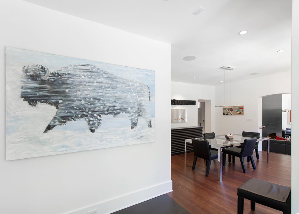 a contemporary painting highlights a modern dining room